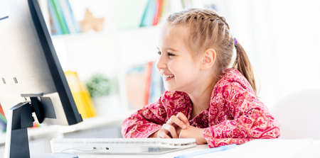 Happy little girl looking at computer screen