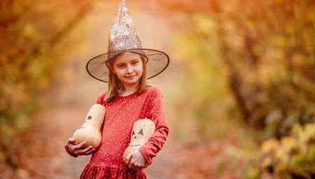 Little girl holding pumpkins for halloween