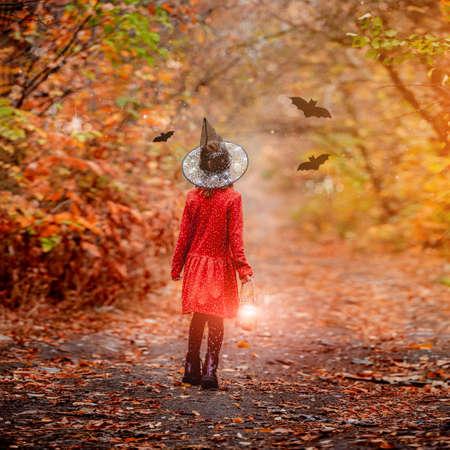 Little girl in witch hat in wood 免版税图像