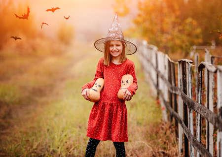 Little girl in holding halloween pumpkins 免版税图像