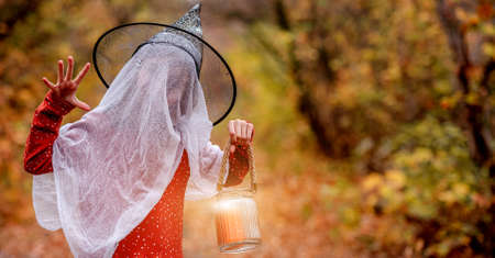 Little girl in halloween costume with candle