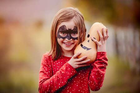 Smiling little girl holding pumpkin above head