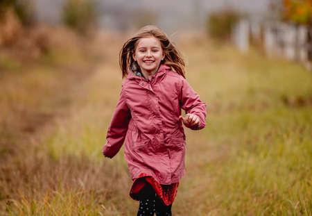 Smiling little girl running in pine forest 免版税图像
