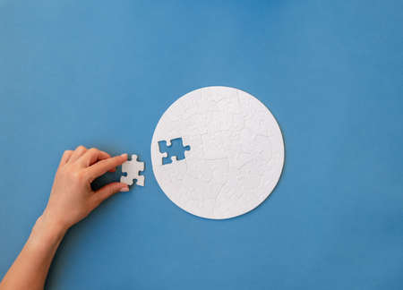 Hand putting piece in round puzzle