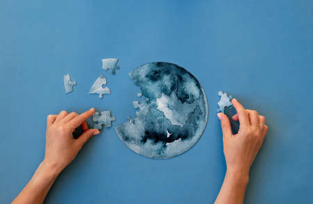 Hands collecting round jigsaw puzzle