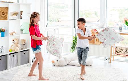 Laughing kids having fun while pillow fight