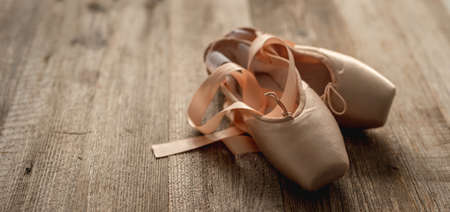 Pointe shoes with ribbons on wooden background