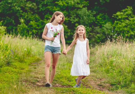 Pretty girls walking on summer meadow