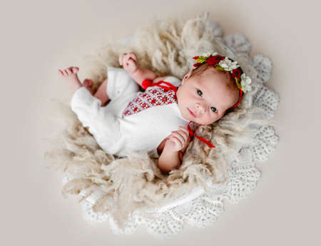 Sleepless newborn in embroidered suit and diadem