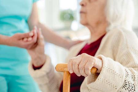 Senior woman hand in caregiver hands Foto de archivo