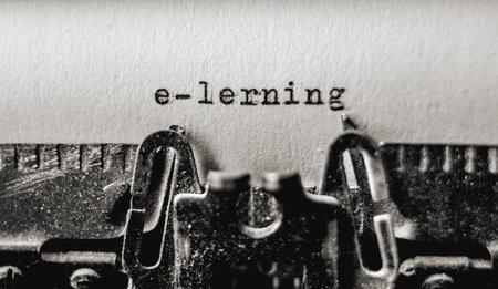 Printed text E-lerning on retro typewriter. Vintage typography font on white paper