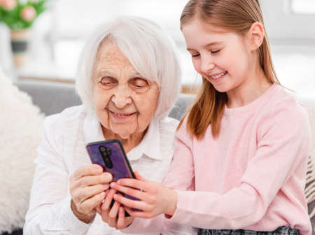 Grandmother with grandaughter using smartphone