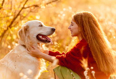 Young girl petting dog in nature