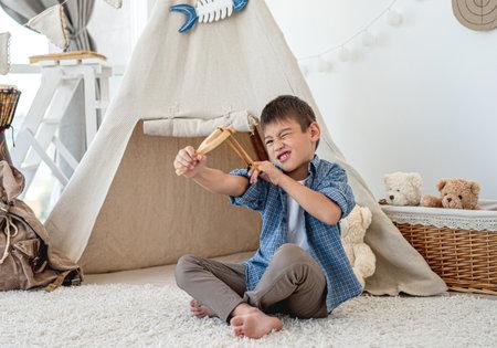 Little boy with wood slingshot