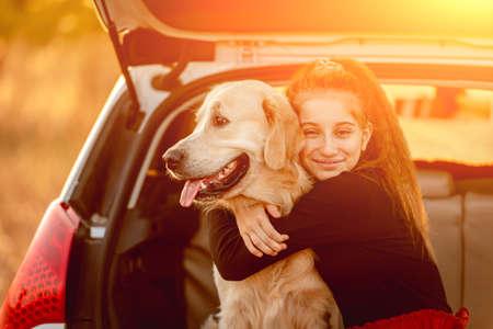 Teenage girl hugging dog in car trunk