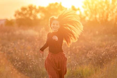 Smiling teenage girl on autumn field 스톡 콘텐츠