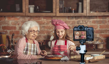 Granny helps her granddaughter with homemade pie