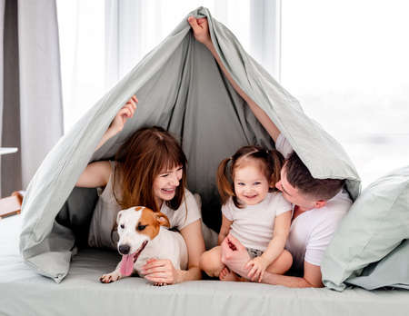 Family under the blanket in the bed