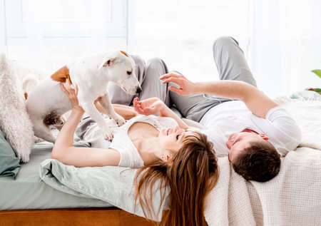 Couple in the bed with dog Archivio Fotografico