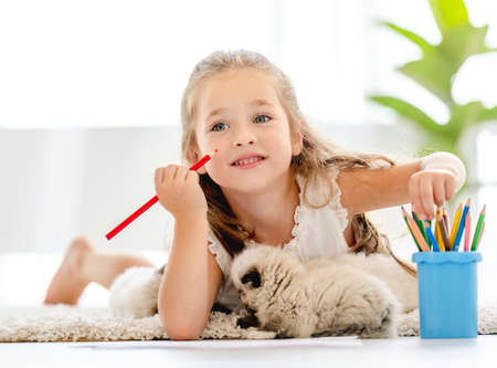 Girl painting with ragdoll kittens Archivio Fotografico
