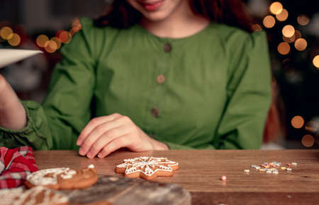 Girl in festive apron decorating gingerbread