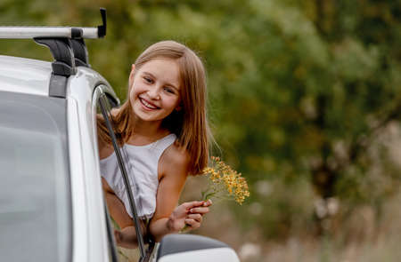 Preteen girl looking from car