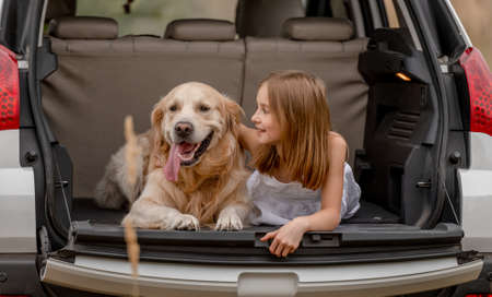 Preteen girl with golden retriever dog in car trunk Banque d'images