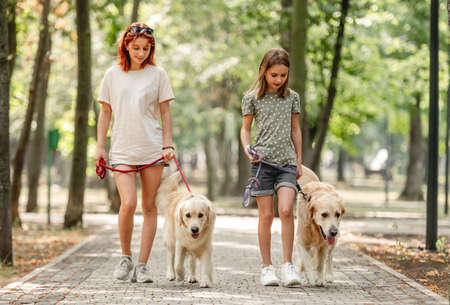 Girls with golden retriever dog