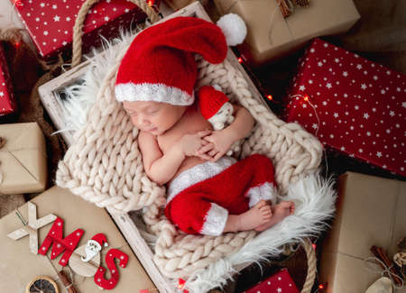 Charming newborn sleeping between christmas presents