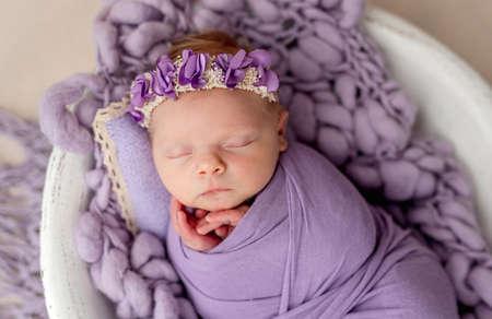 Newborn sleeping wrapped in violet blanket