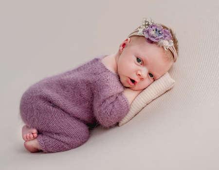 Awake newborn girl with flower diadem