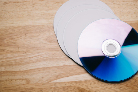 optical disk: Close up view of a CDDVD on wood table, vintage tone