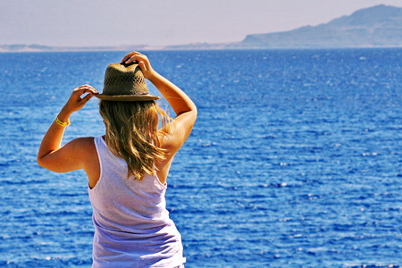far away look: A young woman thoughtfully looks at a sea and holds a hat, hair develop on wind
