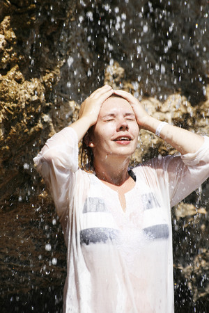 the weakening: A young woman stands under a waterfall laughs