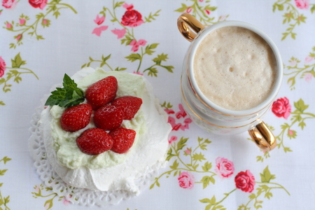 Pavlova cake with strawberries with a cup of cappuccino on a colorful napkin Stock Photo