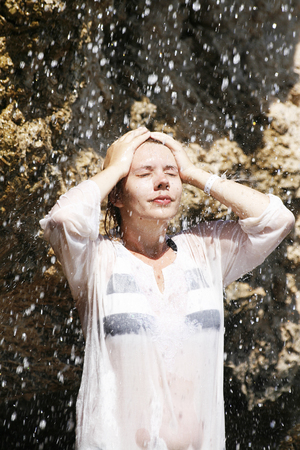 the weakening: A young woman stands on a rock under a waterfall Stock Photo
