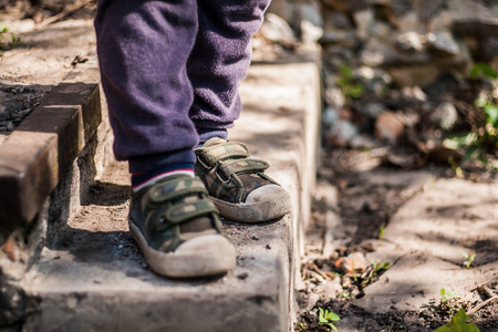 child legs in sneakers on the stairs.