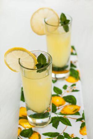 material de vidrio: Limonada en jarra y vasos en la mesa con menta. Foto de archivo
