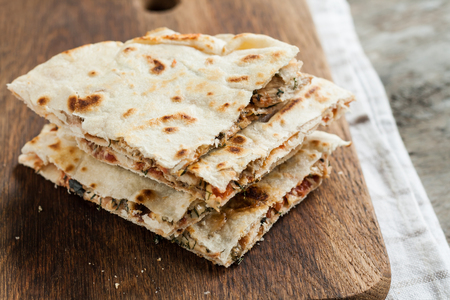 pile of quesadillas with chicken and vegetables on the rustic board.
