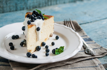 Cottage cheese baked pudding, sour cream and blueberries in a rustic style