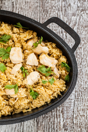 Pilaf rice-curry with chicken and salad in the form of iron. Stock Photo