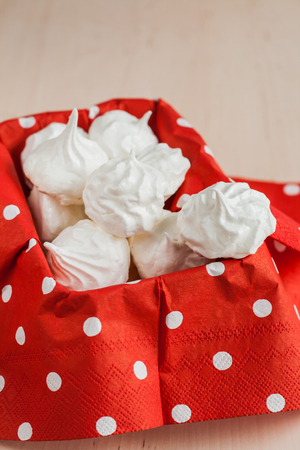 Small meringues meringue on a red background.