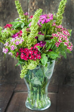 bouquet of garden Turkish carnations in a vase on a wooden background. Stock Photo