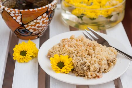 piece of cake with crumbs, tea and yellow flowers on white wooden background.