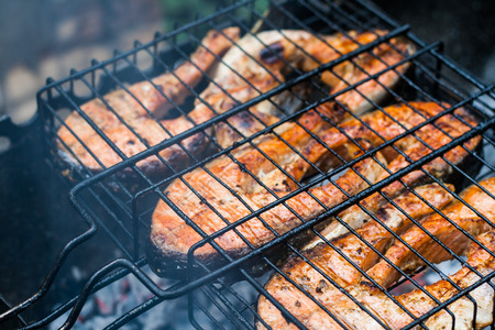 coal fish: Salmon steaks on a lattice barbecue grill.