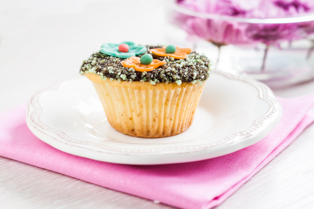 ganache: cupcake with chocolate ganache and decorated with flowers chrysanthemums. Stock Photo