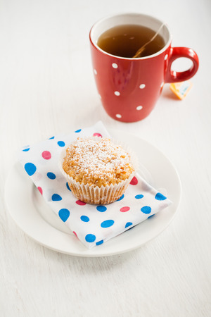 vanilla muffin-cake dusted with powdered sugar and red tea cup.