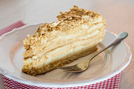 cut piece of cake napoleon with a fork on a plate.