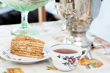 piece of cake honey cake on a plate, a cup of tea and a samovar. Stock Photo