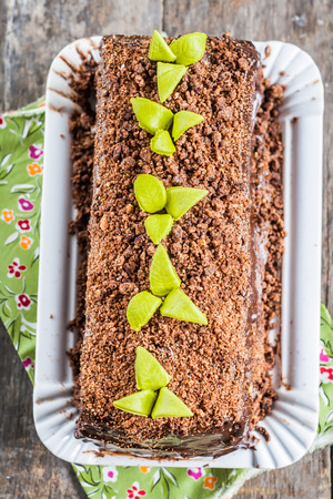 Chocolate cake in the form of logs decorated with chocolate chips and leaves of fondants.